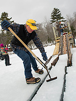 John Jurczynski guides several ice blocks from the channel with their pulley system chute to load into the waiting trucks as volunteers work to fill two ice houses at the Rockywald Deephaven Camps for use next summer.  (Karen Bobotas/for the Laconia Daily Sun)