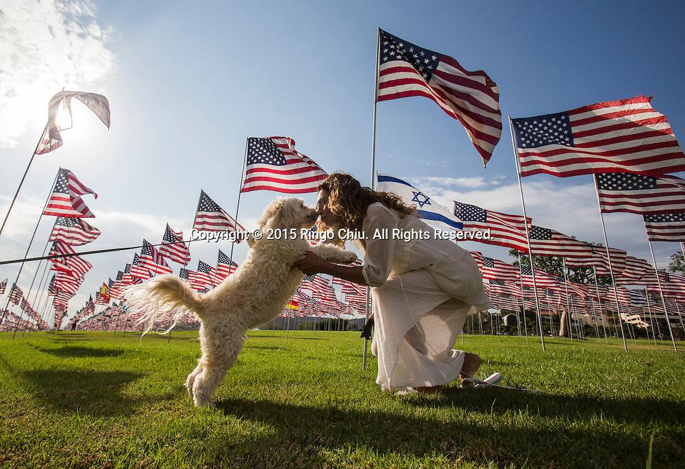 9月10日,在美国加利福尼亚州洛杉矶的马里布,一名女子亲吻她的狗。当天,在美国&ldquo;9&middot;11&rdquo;事件十四周年前夕,佩珀代因大学的学生和教职员工在学校草坪上插起约3000面美国国旗,纪念&ldquo;9&middot;11&rdquo;事件遇难者。新华社发(赵汉荣摄)<br /> A woman kisses her dog amongst 3,000 US flags are displayed at Pepperdine University to mark the 14th anniversary of the 9/11 terror attack, September 10, 2015 in Los Angeles, California, the United States. (Xinhua/Zhao Hanrong)Photo by Ringo Chiu/PHOTOFORMULA.com)