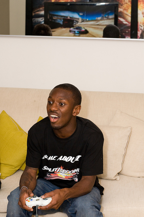 England footballer Sean Wright-Phillips playing computer games on the sofa as part of a promotion for a Disney computer Game called Split Second.