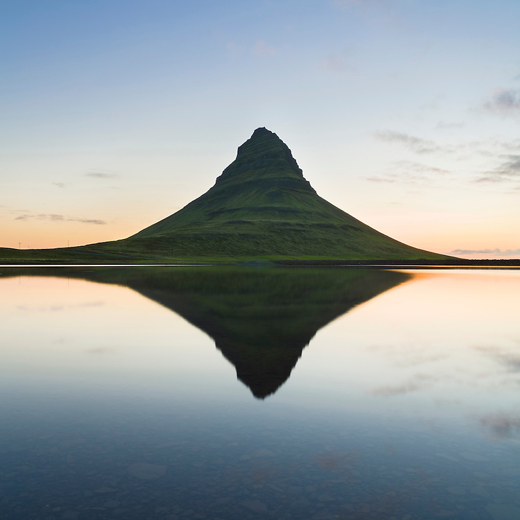 Mt. Kirkjufell reflected in a lake at night.