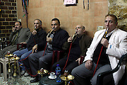 Israel, Jerusalem, Old City, Five Arab men smoke a nargileh in a cafe