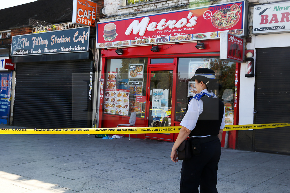 © Licensed to London News Pictures. 14/09/2019. London, UK. Police officer guards a crime scene on Downham Way in Lewisham as a murder investigation has been launched by Met Police after a 34 years old man died in hospital. The victim suffered stab and head wounds on Friday 13 Sept following a fight inside Metro chicken shop on Downham way. A 51 year old man was also injured in the fight and has since been discharged from hospital and subsequently arrested in suspicion murder. Two other men aged 40 and 46 have also been arrested on suspicion murder. Photo credit: Dinendra Haria/LNP