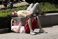 © Licensed to London News Pictures. 19/05/2014. London, UK. Two men relax in the sunshine on the side of the street near St Paul's Cathedral in London at lunchtime on 19th May 2014. Photo credit : Vickie Flores/LNP