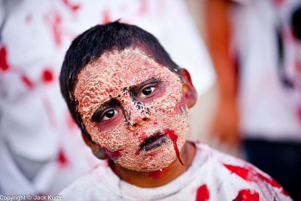"""Oct. 30, 2009 -- PHOENIX, AZ: ALEX NUMKENA, 7, from Phoenix, AZ, shuffles through downtown Phoenix during the city's """"Zombie Walk."""" About 200 people participated in the first """"Zombie Walk"""" in Phoenix, AZ, Friday night. The Zombies walked through downtown Phoenix """"attacking"""" willing victims and mixing with folks going to the theatre and downtown sports venues.  Photo by Jack Kurtz"""