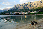 Two children (9 years old and 5 years old) squatting on beach, with the Biokovo National Park, part of the Dinaric Alps, in the background. Makarska, Croatia