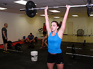 Owner Jason Hoskins of Dayton (left) and Nicole Hughes of Dayton (right) during a workout of the day session at Vigor Crossfit in Moraine, Wednesday, January 25, 2012.