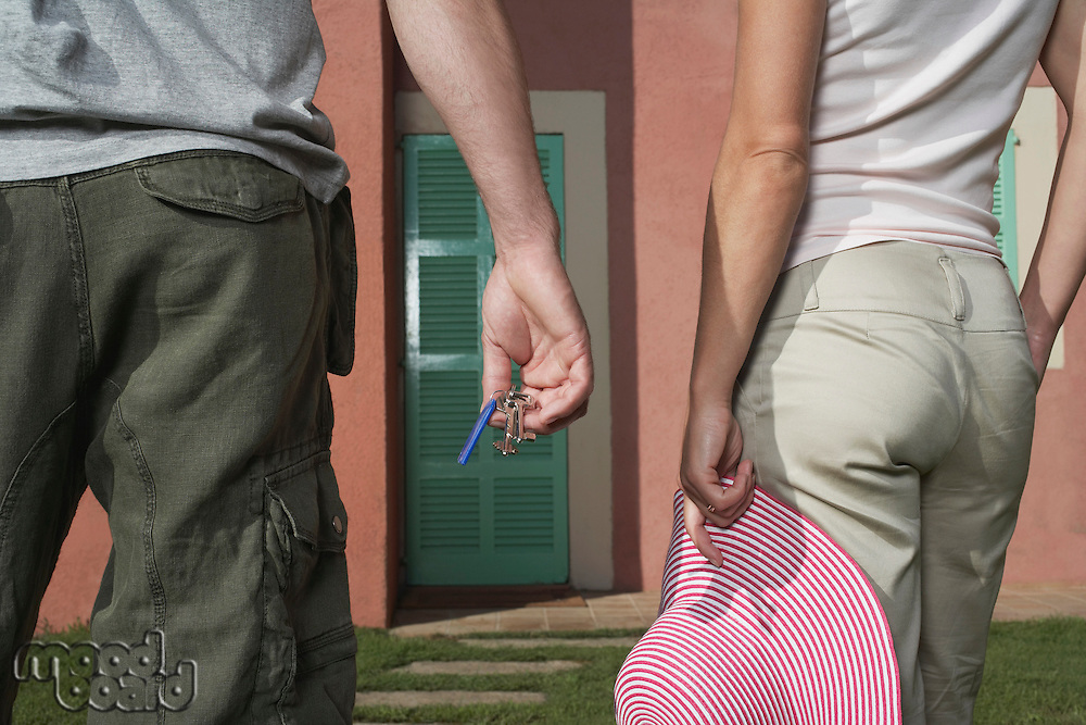 Man and woman in front of house man holding keys woman hat
