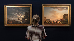 "© Licensed to London News Pictures. 01/07/2016. London, UK.  A staff member views (L to R) ""Clair de lune"" and ""Le Soir"" both by Claude-Joseph Vernet (est. GBP 3-5 million for the pair), at the preview of Sotheby's London Old Masters evening sale which takes place 6 July.   Photo credit : Stephen Chung/LNP"