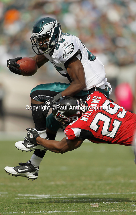 Philadelphia Eagles running back LeSean McCoy (25) tries to leap over the defender as he gets upended by Atlanta Falcons cornerback Brian Williams (29) during the NFL week 6 football game against the Atlanta Falcons on Sunday, October 17, 2010 in Philadelphia, Pennsylvania. The Eagles won the game 31-17. (©Paul Anthony Spinelli)