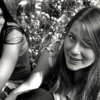 Two teenage girls sitting in a field of flowers
