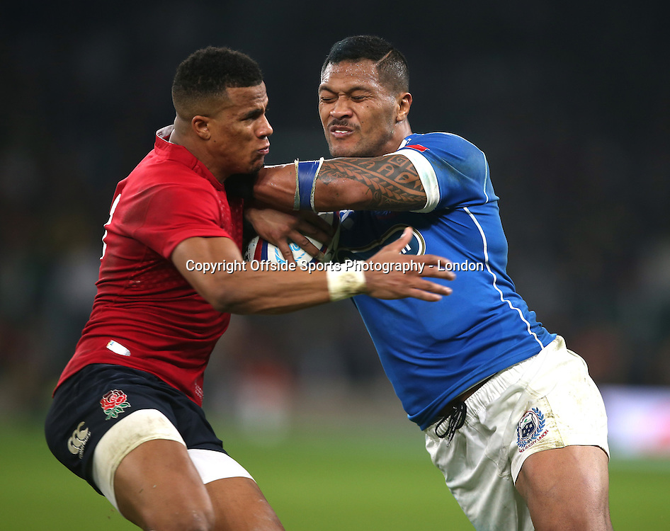 22 November 2014 International Rugby Union - England v Samoa;   Anthony Watson of England (red) tackles John Leota of Samoa.<br /> Photo: Mark Leech