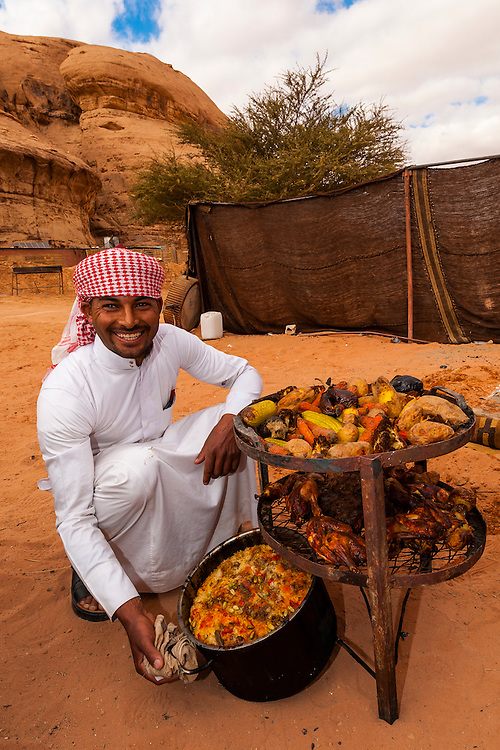 Bedouin man with a meal cooking in a pit in the ground, Captain's Desert Camp, Wadi Rum (in the Arabian Desert), Jordan