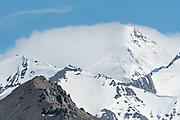 Snow blows on the summit of a mountain in the Alaska Range in Denali National Park Alaska. Denali National Park and Preserve encompasses 6 million acres of Alaska's interior wilderness.