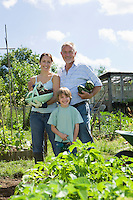 Family with boy holding vegetables in garden portrait