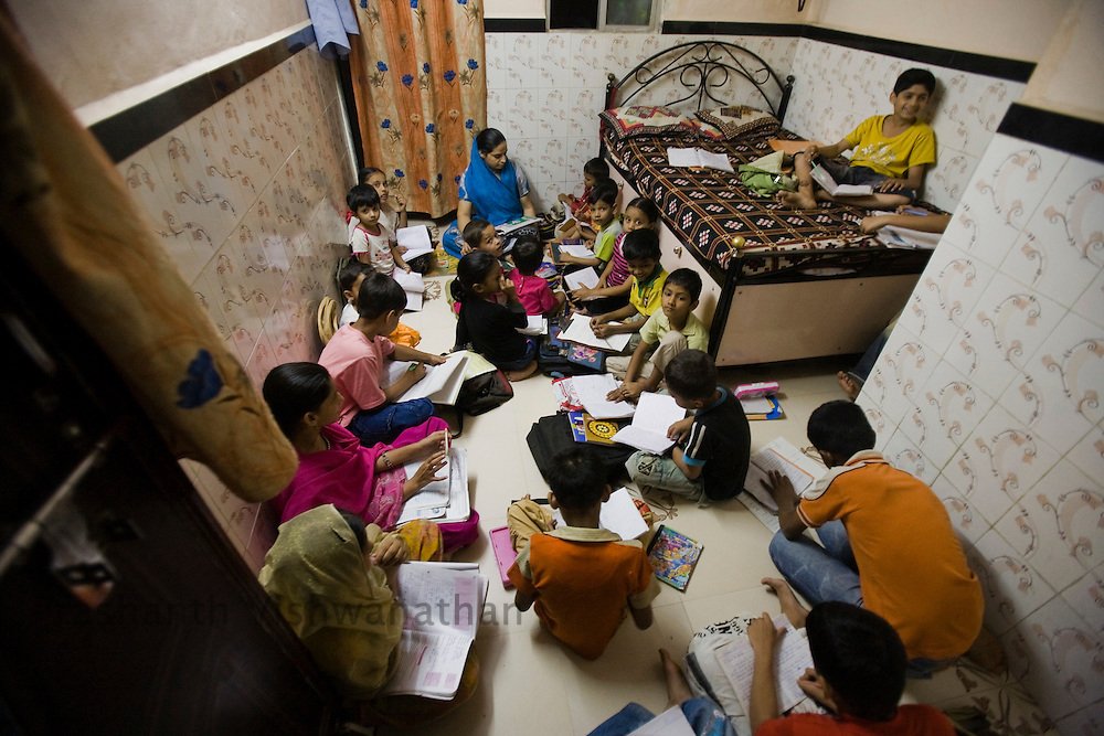A women mandal activist conducts tution classes in her one room bedroom premises of the Razzaq chawl area, in Mumbai, India, on Monday February 10, 2009