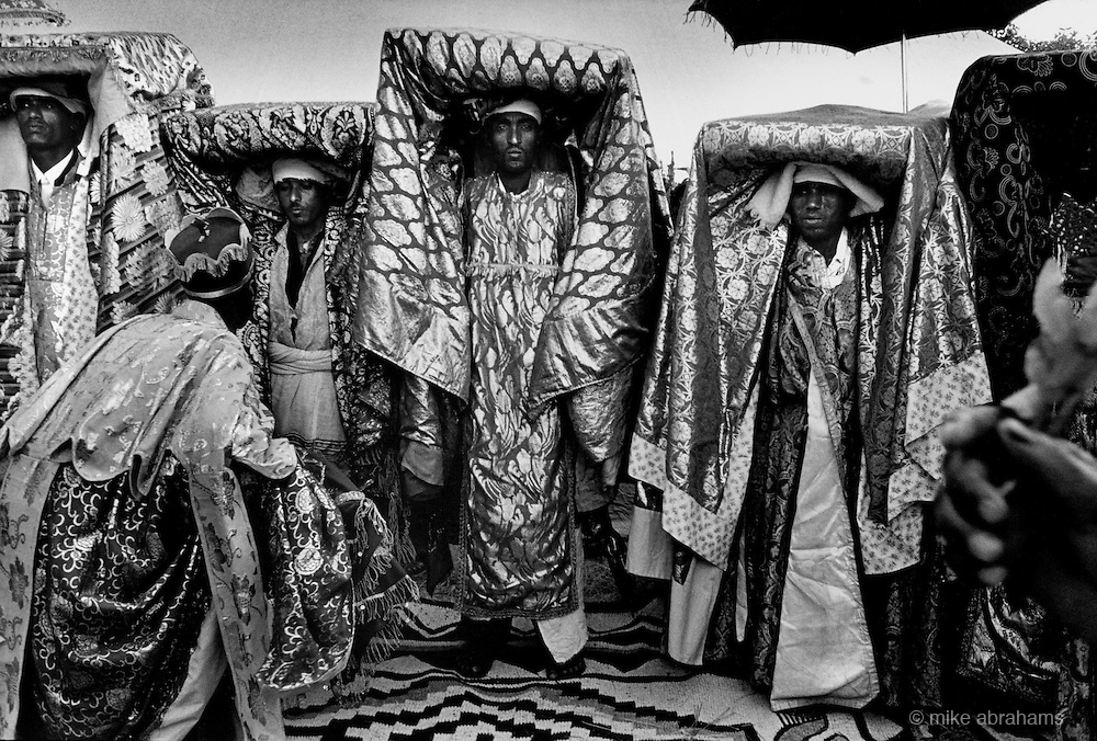 Ethiopian Orthodox pilgrims at Lalibela, Ethiopia. Priests carrying a Tabot, a model of The Ark of the Covenant wrapped in a rich cloth and carried on the head of the priest is assisted by a deacon holding a liturgical parasol. Lalibela in northern Ethiopia is famous for it's monolithic roack hewn churches and is one Ethiopia's holiest cities and a centre of pilgrimage for much of the country.