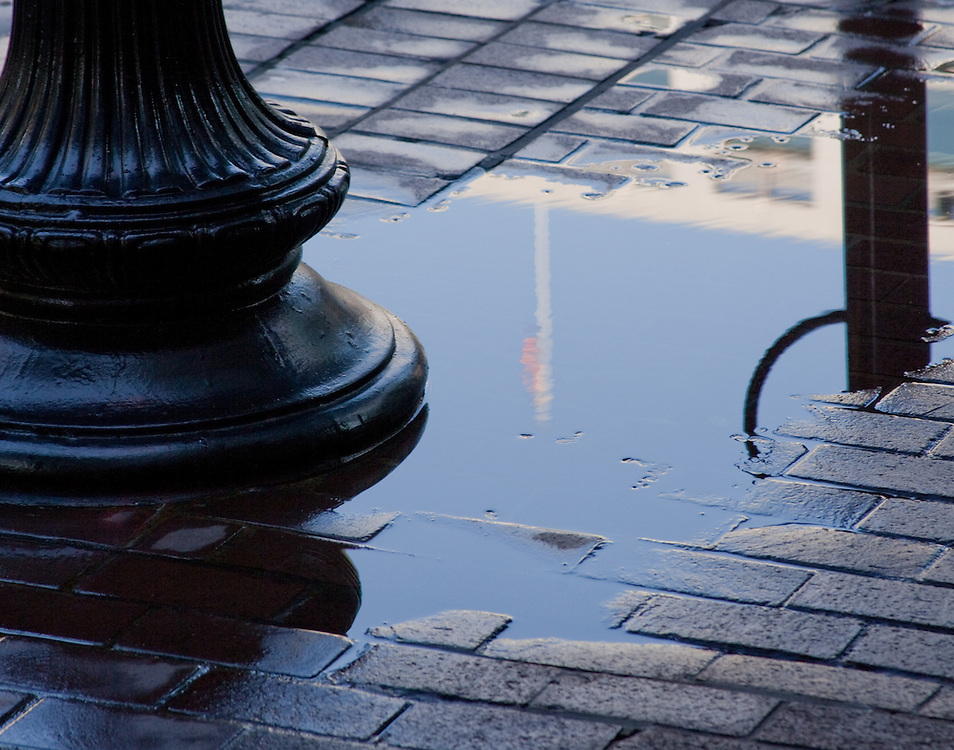 Ponding water on a brick sidewalk reflects the base of a lightpole and an American flag.