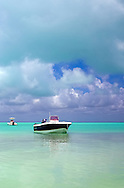 Small boats on green tropical waters under a partly cloudy blue sky WATERMARKS WILL NOT APPEAR ON PRINTS OR LICENSED IMAGES.