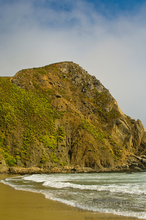 Ocean waves breaking on sand shore below coastal cliff and fog at Pfeiffer Beach, Big Sur Coast, Monterey County, California