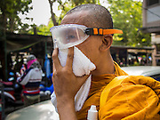 26 DECEMBER 2013 - BANGKOK, THAILAND:   A Buddhist monk covers his nose against tear gas while he takes shelter in an apartment block near the Thai Japan Stadium. Thousands of anti-government protestors flooded into the area around the Thai Japan Stadium to try to prevent the drawing of ballot list numbers by the Election Commission, which determines the order in which candidates appear on the ballot of the Feb. 2 election. They were unable to break into the stadium and ballot list draw went as scheduled. The protestors then started throwing rocks and small explosives at police who responded with tear gas and rubber bullets. At least 20 people were hospitalized in the melee and one policeman was reportedly shot by anti-government protestors.    PHOTO BY JACK KURTZ