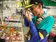 08 JANUARY 2015 - BANGKOK, THAILAND:  A man uses a jeweler's loupe to look at an amulet in a street side stall. Hundreds of vendors sell amulet and Buddhist religious paraphernalia to people in the Amulet Market, an area north of the Grand Palace near Wat Maharat in Bangkok.            PHOTO BY JACK KURTZ