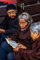 Elderly Chinese women reading prayer books, Yuantong Temple is the most famous Buddhist temple in Kunming, Yunnan Province, China. It was first built in the late 8th and early 9th century, the time of the Nanzhao Kingdom in the Tang dynasty.