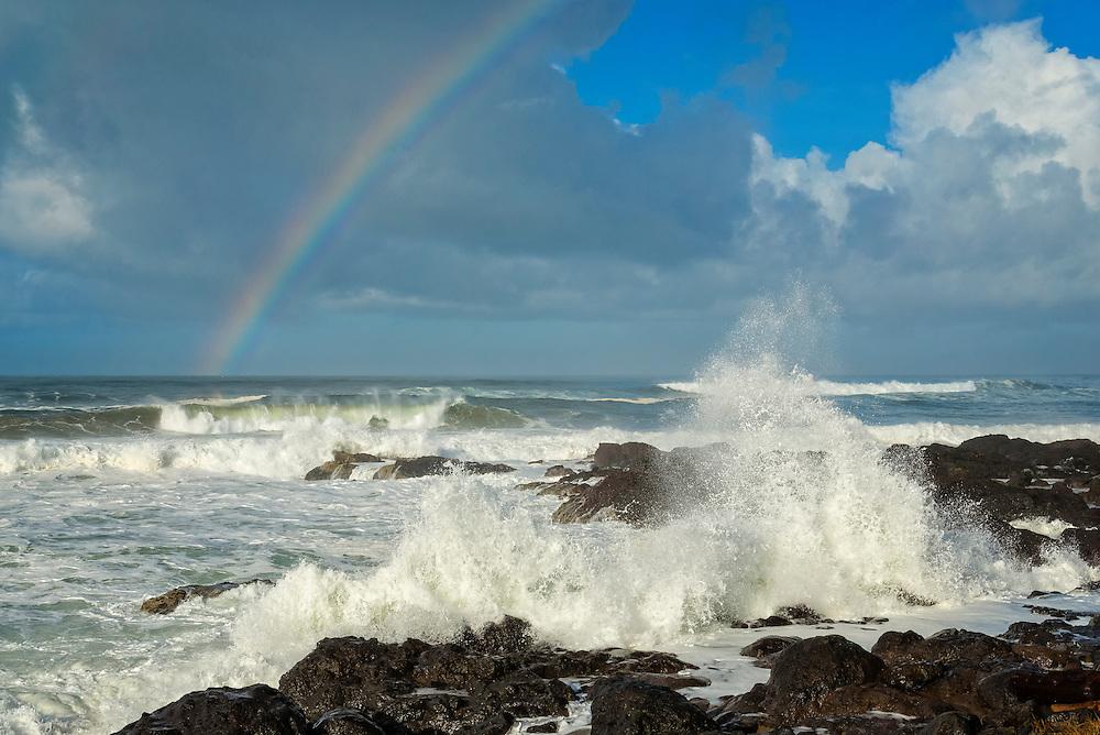 Rainbow and surf hitting shoreline rocks at Yachats, central Oregon Coast.