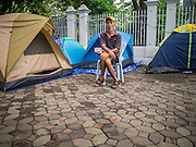 23 NOVEMBER 2012 - BANGKOK, THAILAND:   A Pitak Siam anti-government protester sits near his tent in Bangkok Friday. Thai authorities have imposed the Internal Security Act (ISA), that enables police to call on the army if needed to keep order, and placed thousands of riot police in the streets around Government House in anticipation of a large anti-government protest Saturday. The group sponsoring the protest, Pitak Siam, said up to 500,000 people could turn out to protest against the government. They are protesting against corruption in the current government and the government's unwillingness to arrest or pursue fugitive former Prime Minister Thaksin Shinawatra, deposed in 2006 coup and later convicted on corruption charges. The current Thai Prime Minister is Yingluck Shinawatra, Thaksin's sister.     PHOTO BY JACK KURTZ