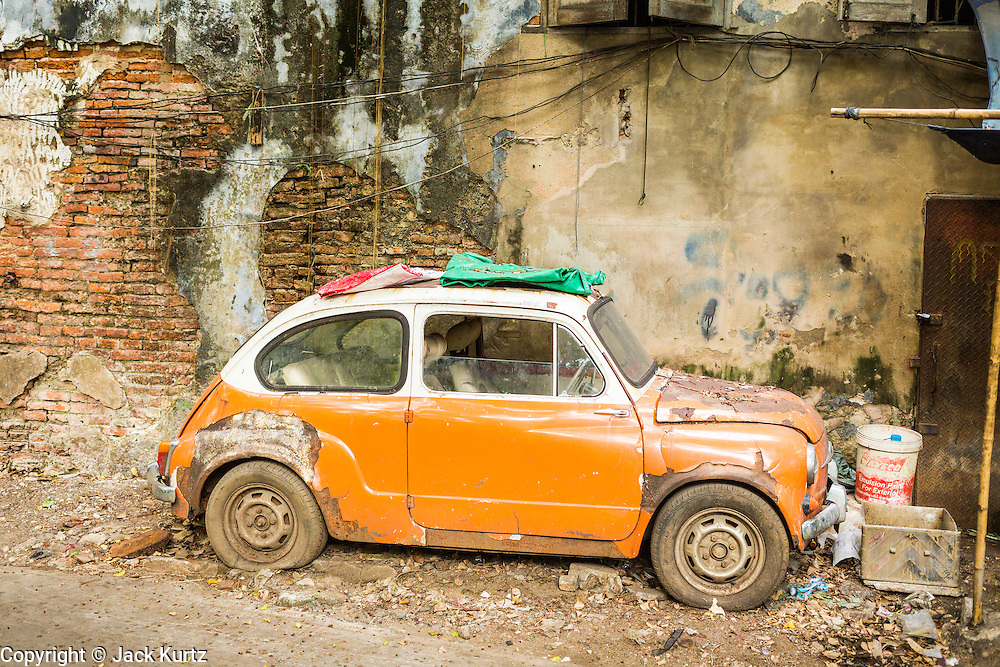 27 APRIL 2013 - BANGKOK, THAILAND:   An inoperable Fiat 500 parked against a wall in Talat Noi. The Talat Noi neighborhood in Bangkok started as a blacksmith's quarter. As cars and buses replaced horse and buggy, the blacksmiths became mechanics and now the area is lined with car mechanics' shops. It is one the last neighborhoods in Bangkok that still has some original shophouses and pre World War II architecture. It is also home to a  Teo Chew Chinese emigrant community.         PHOTO BY JACK KURTZ