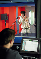 Young woman singing in studio technician in foreground
