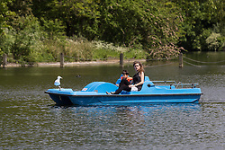 © Licensed to London News Pictures. 14/05/2014. London, UK. A woman and child paddle boating on the lake and enjoying the sunshine and good weather in Regents Park in London on 14th May 2014.. Photo credit : Vickie Flores/LNP