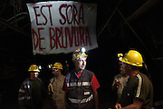 "Miners of the Carbosulcis guard the mine 400 meters under the ground during the occupation undertaken to protest against its foreseen closure near a banner where is written in Sardinian language ""Is time for esplosive""."