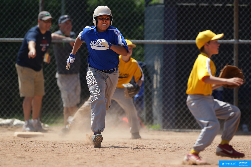 A young baseball player runs towards second base during the Norwalk Little League baseball competition at Broad River Fields,  Norwalk, Connecticut. USA. Photo Tim Clayton