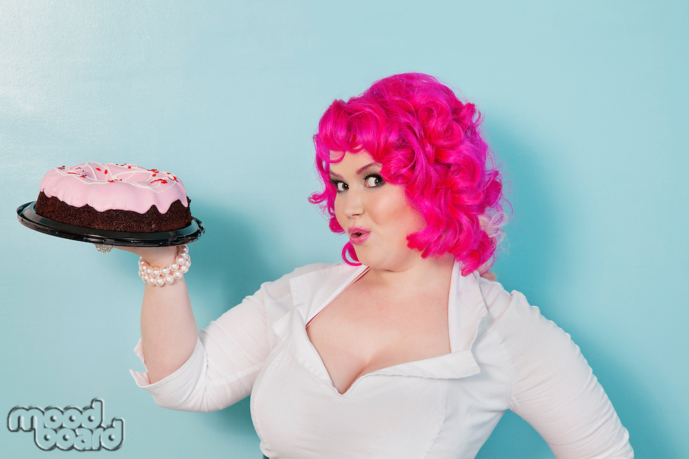 Portrait of happy woman showing cake over colored background