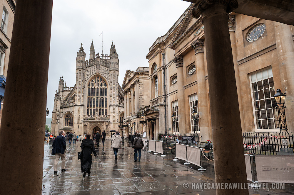 Tourists on a rainy day in central Bath in front of the entrance to the historic Roman baths, with the West Front of Bath Abbey in the background.