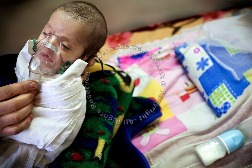 Khadija, 27 days, a young girl with a severe heart defect, is breathing through an aerosol while in her mother's arms, inside a room of the children's ward at Fallujah General Hospital, Iraq.