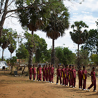 A sports class in the grounds of the Thikilivattai Government Tamil Mixed School in Batticaloa District. <br /> <br /> Thikilivattai Government Tamil Mixed School reopened in May 2008 after local conflict between the LTTE and SLA  troops eased. There are now 351 students in grades 1-9 with a teaching staff of 18. The school has no water supply. Though many of the pupils' parents are not well educated themselves (most are employed in casual paddy cultivation, fishing and seasonal day-wage labour), there is a parents' mobilisation committee that encourages pupil attendance and is involved in helping keep the school clean. The school has an active sports department. Many of the students suffer with the trauma and stress associated with those living in conflict situations. The staff must deal with these issues as well as the personal difficulties that they themselves suffer living in a conflict environment. UNICEF have provided three temporary learning spaces to make up for the lack of space in the original school building. A further two classes must be accommodated beneath trees. UNICEF have also supplied the school furniture.<br /> <br /> Photo: Tom Pietrasik<br /> Batticaloa District, Sri Lanka<br /> September 30th 2009