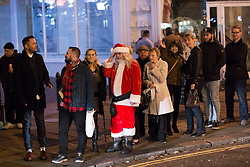 "© Licensed to London News Pictures. 19/12/2014. Brighton, UK. Santa Claus waits in the queue for a taxi  after going out on ""Mad Friday"" night in Brighton East Sussex (19/12/2014). Across the UK thousands of people begin 2 weeks of festivities over the Christmas Period. Photo credit : Hugo Michiels/LNP"
