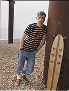 Young man leaning against wood pole with longboard skateboard next to him.