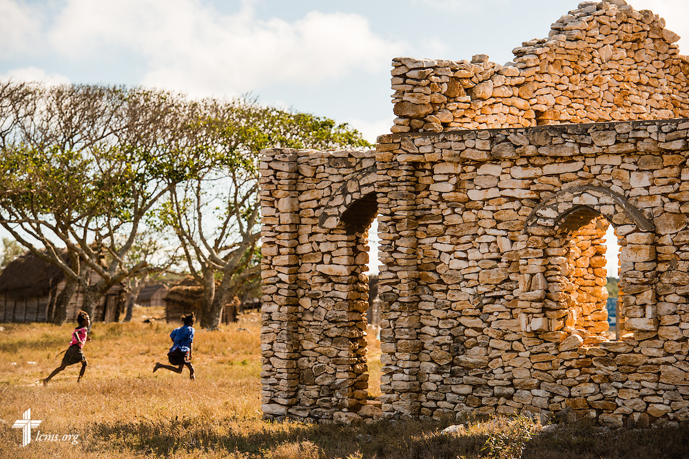 Children run past a Fiangonana Loterana Malagasy (FLM, Malagasy Lutheran Church) church near Tsiombe, southern Madagascar, on Tuesday, Oct. 21, 2014. The stone church is awaiting a new tin roof. LCMS Communications/Erik M. Lunsford