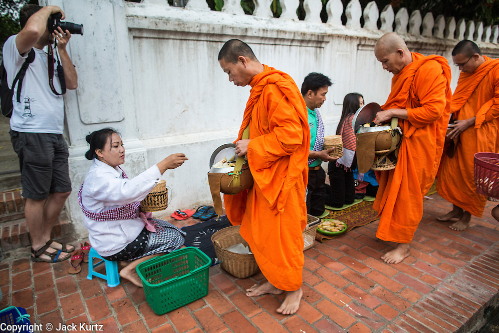 """11 MARCH 2013 - LUANG PRABANG, LAOS:  A tourist photographs Buddhist monks collecting alms during the tak bat in Luang Prabang. The """"Tak Bat"""" is a daily ritual in most of Laos (and other Theravada Buddhist countries like Thailand and Cambodia). Monks leave their temples at dawn and walk silently through the streets and people put rice and other foodstuffs into their alms bowls. Luang Prabang, in northern Laos, is particularly well known for the morning """"tak bat"""" because of the large number temples and monks in the city. Most mornings hundreds of monks go out to collect alms from people.   PHOTO BY JACK KURTZ"""