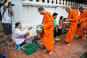 "11 MARCH 2013 - LUANG PRABANG, LAOS:  A tourist photographs Buddhist monks collecting alms during the tak bat in Luang Prabang. The ""Tak Bat"" is a daily ritual in most of Laos (and other Theravada Buddhist countries like Thailand and Cambodia). Monks leave their temples at dawn and walk silently through the streets and people put rice and other foodstuffs into their alms bowls. Luang Prabang, in northern Laos, is particularly well known for the morning ""tak bat"" because of the large number temples and monks in the city. Most mornings hundreds of monks go out to collect alms from people.   PHOTO BY JACK KURTZ"