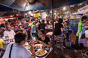 18 SEPTEMBER 2013 - BANGKOK, THAILAND:  People eat at a seafood stand in the Chinatown section of Bangkok. Lek and Rut Seafood was one of the first street stall restaurants in Bangkok and is more of a pop up restaurant than a street food stall. It has sit down service and full menus, but seating is on the street and sidewalk and food is prepared in portable cookers that are brought out to the street when the restaurant opens. Thailand in general, and Bangkok in particular, has a vibrant tradition of street food and eating on the run. In recent years, Bangkok's street food has become something of an international landmark and is being written about in glossy travel magazines and in the pages of the New York Times.     PHOTO BY JACK KURTZ