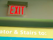Exit sign to escalator and signs in a subway station.