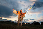 Native American medicine man dressed in ghost shirt shakes wooden staff towards sky