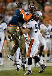 Virginia defensive coordinator congratulates Virginia linebacker Jon Copper (54) after he intercepted a Miami (FL) quarterback Kyle Wright (3) pass.  The #19 Virginia Cavaliers defeated the Miami Hurricanes 48-0 at the Orange Bowl in Miami, Florida on November 10, 2007.  The game was the final game played in the Orange Bowl.