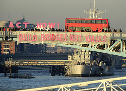 © Licensed to London News Pictures. 20/01/2017. London, UK.  As part of the 'Bridges not Walls' campaign of national demonstrations against Donald Trump, a banner is suspended from Tower Bridge. Donald Trump will attend his inauguration ceremony in Washington today. Photo credit: Peter Macdiarmid/LNP