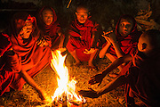 Buddhist monks warming themselves by pre-dawn fire before full moon festival, Mandalay, Myanmar