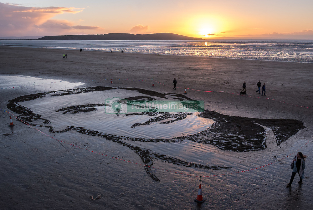 """November 11, 2018 - Weston-Super-Mare, North Somerset, UK - Weston-super-Mare, North Somerset, UK. Pages of the Sea on the Armistice Day centenary, 1918-2018, of the end of the First World War. Pictured: a sand portrait of Lieutenant Colonel John Hay Maitland Hardyman, designed by sand artists Sand In Your Eye,  drawn into the sand on Weston's beach to be washed away as the tide comes in. Lieutenant Colonel John Hay Maitland Hardyman, D.S.O. M.C. (28 September 1894 – 24 August 1918) was born in Bath, was an Officer in the Royal Flying Corps and was awarded for gallantry. In May 1918, aged only 23, he became the youngest lieutenant colonel in the British Army. In December 1914, he was accepted for officer training with the Royal Flying Corps (forerunner of the RAF) at Brooklands, Surrey, though eventually served with the Somerset Light Infantry. He was awarded the Distinguished Service Order for conspicuous gallantry and devotion to duty. After the enemy had penetrated allied lines, John went forward through a heavy barrage to rally the troops and repel repeated enemy attacks over two days and three nights. He encouraged them through """"coolness and absolute disregard of personal danger"""" to maintain a tactically important position. He was killed in action at Bienvillers, France, and buried in the military cemetery there. He was killed in France aged 24. Pages of the sea was devised by film-maker Danny Boyle and held at over 30 beaches across the UK on 11th November. Each event centres around a drawing of a large-scale portrait of a casualty from the First World War, designed by local sand artists, which will be washed away as the tide comes in. (Credit Image: © Simon Chapman/London News Pictures via ZUMA Wire)"""