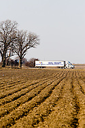 Delivering goods to it's many stores, a Wal-Mart truck heads down I-88 through a barren winter/spring landscape.